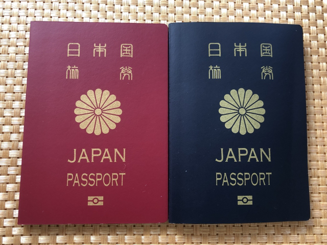 赤色のパスポートと青色のパスポートを並べた画像