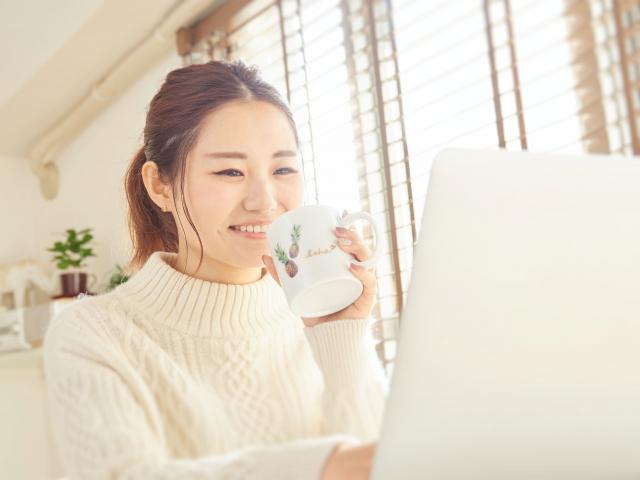 ホットドリンクを飲みながらパソコン作業をする女性