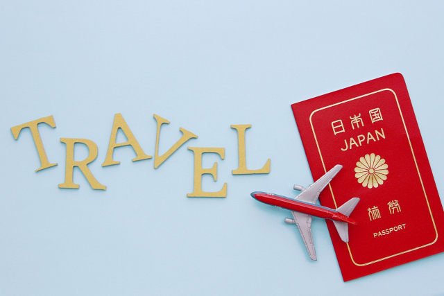 飛行機の模型とパスポートが置かれている画像