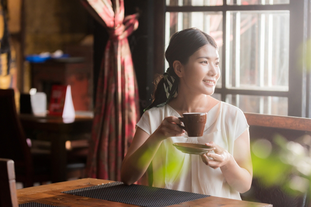 カフェで一人でコーヒーを飲んでいる女性